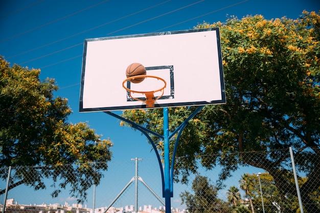 Basketbal die in hoepel op blauwe hemel vallen