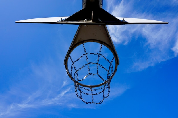 Basketbal hoepel met metalen net en blauwe lucht op straat