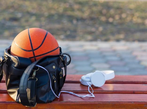 Basketbal in een tas met koptelefoon