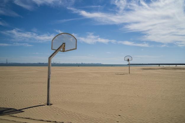 Basketbal ringen op het strand met een bewolkte blauwe hemel