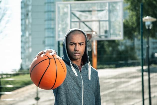 Basketbal spel. aardige knappe man die naar je kijkt terwijl je basketbal speelt
