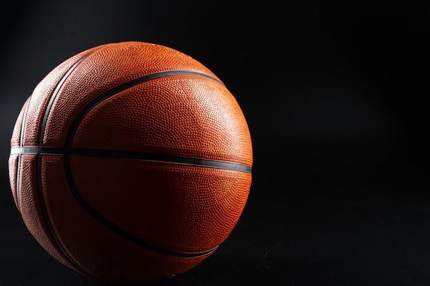 Basketbalbal dichte omhooggaand op donkere zwarte achtergrond. basketbal concept
