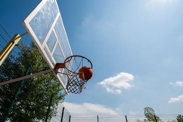 Basketbalbal in schot van de hoepel het lage hoek