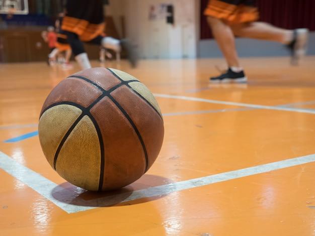 Basketbalbal op het veld met vrije worplijn, onscherpe spelers