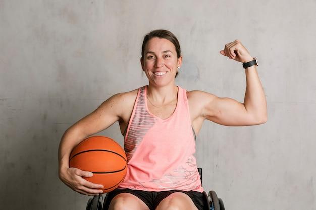 Basketballer in een rolstoel die haar armen buigt