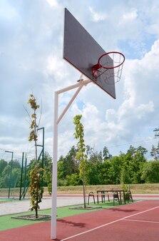 Basketbalpaal met een mand in een stadion buiten. verticale weergave. lage kijkhoek