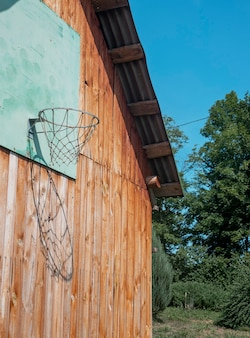 Basketbalring in de natuur in de zomer houten muur van huis met net om te spelen