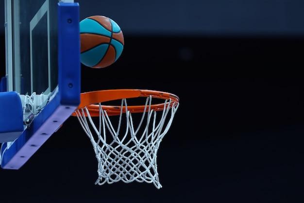 Basketbalring met een net waarin de bal op een donkere achtergrond vliegt