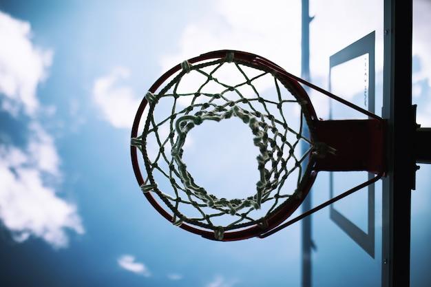 Basketbalring met net onder blauwe lucht en witte wolken