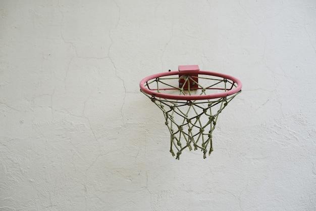 Basketbalring met net tegen een witte muur buiten