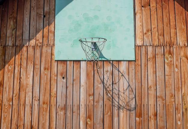 Basketbalring op houten muur van huis met net voor het spelen van zonlicht en schaduw
