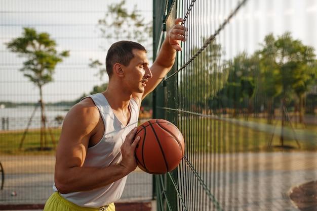 Basketbalspeler die zich bij het gaasomheining bevindt