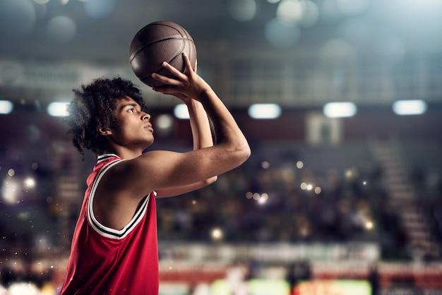 Basketbalspeler gooit de bal in de basket in het stadion vol met toeschouwers