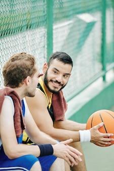 Basketbalspeler kijken naar pratende vriend