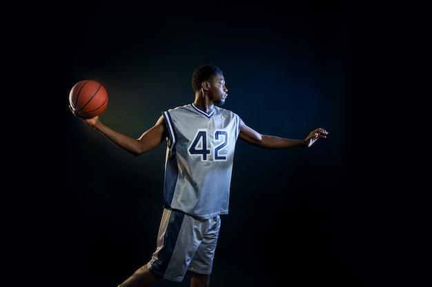 Basketbalspeler met bal, oefenen in actie in studio, zwarte achtergrond. professionele mannelijke baller in sportkleding die sportspel speelt.