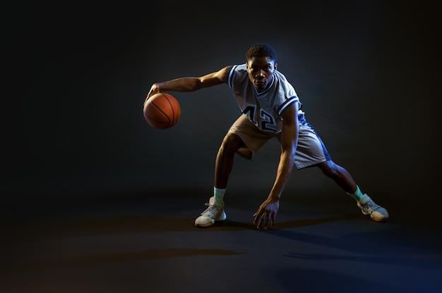 Basketbalspeler met bal, oefenen in actie. professionele mannelijke baller in sportkleding die sportspel speelt, lange sportman