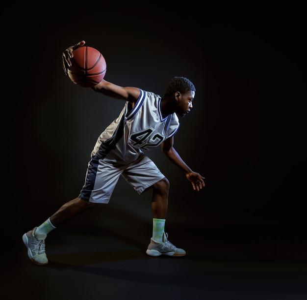 Basketbalspeler met bal, oefenen in actie. professionele mannelijke baller in sportkleding die sportspel speelt, sportman