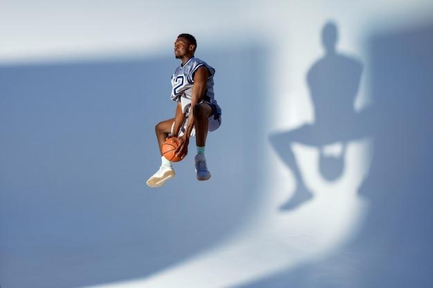 Basketbalspeler met bal toont zijn vaardigheid, hoogspringen in actie. professionele mannelijke baller in sportkleding die sportspel speelt, lange sportman