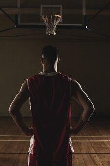 Basketbalspeler met zijn handen op zijn heupen
