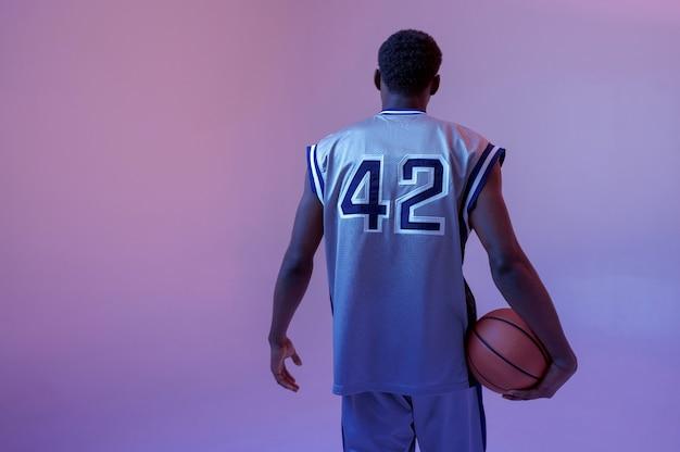 Basketbalspeler poseert met bal in studio, achteraanzicht. professionele mannelijke baller in sportkleding die sportspel speelt, lange sportman