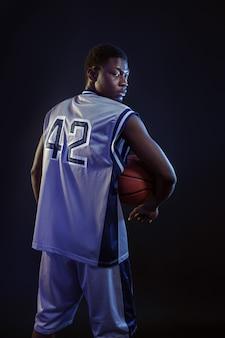 Basketbalspeler poseert met bal in studio, achteraanzicht, zwarte achtergrond. professionele mannelijke baller in sportkleding die sportspel speelt, lange sportman