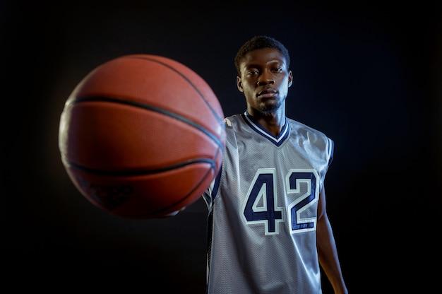 Basketbalspeler toont een bal. professionele mannelijke baller in sportkleding die sportspel speelt, lange sportman