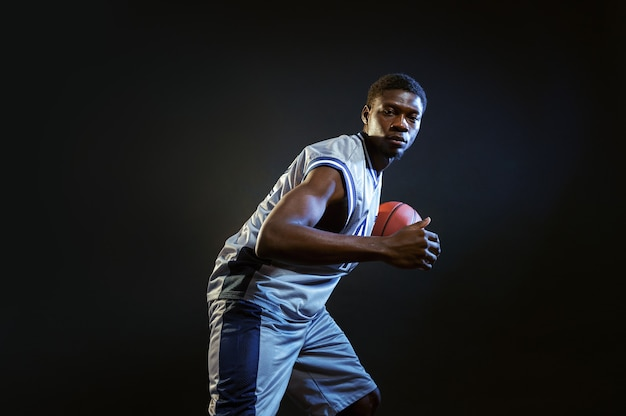 Basketbalspeler, training met bal. professionele mannelijke baller in sportkleding die sportspel speelt, lange sportman