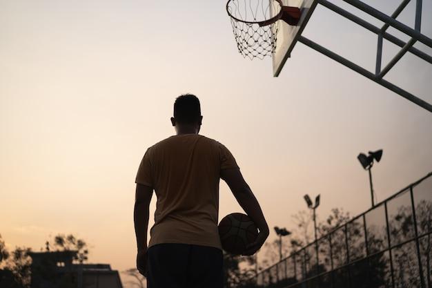 Basketbalspeler traint en traint buiten op de plaatselijke rechtbank