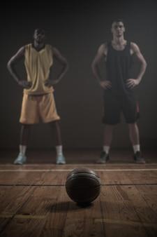 Basketbalspelers die met handen op heupen achter een bal stellen