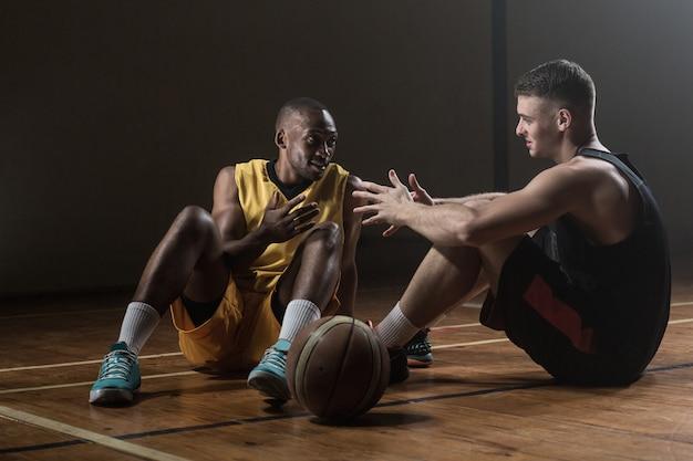 Basketbalspelers zittend op de vloer samen praten