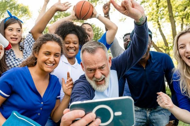 Basketbalsupporters kijken hoe hun team de wedstrijd wint op een mobiele telefoon