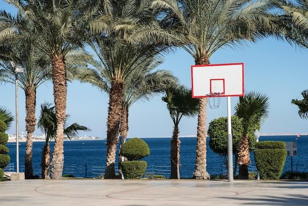 Basketbalveld bij de palmbomen aan zee
