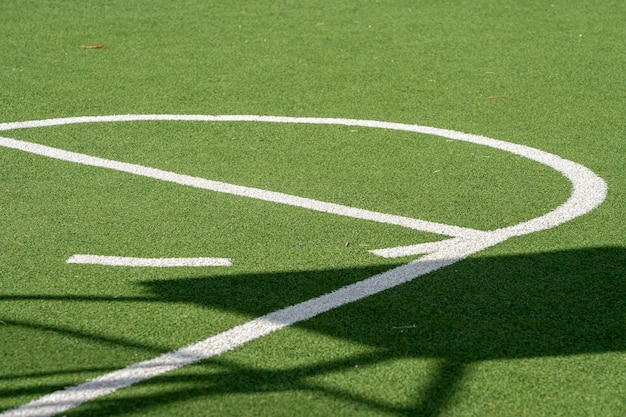 Basketbalveld met groen grasveld, kunstgras en witte lijnen