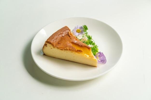 Baskische verbrande cheesecake-decoratoin met bloemen op witte plaat