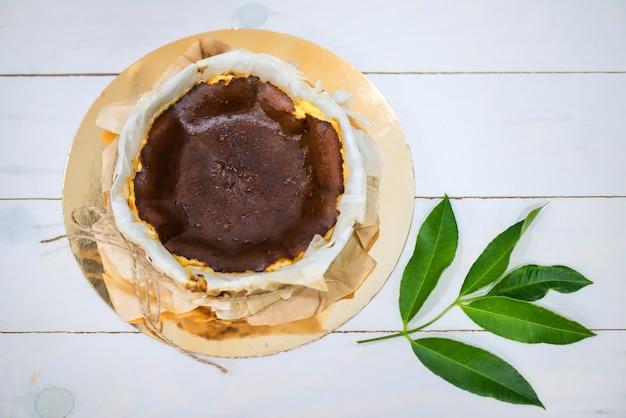 Baskische verbrande cheesecake verpakt door perkamentpapier op witte houtverf met natuurlijk groen blad door antenne