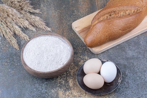 Baton brood op een bord naast tarwe stengels meel kom en eieren op marmeren oppervlak