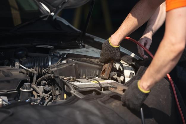 Batterijlader en auto in autoreparatiewerkplaats, automonteur die in garage werkt. reparatie service.