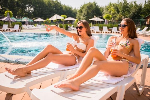 Bautiful vrouwen liggen op chaise-longue bij het zwembad.