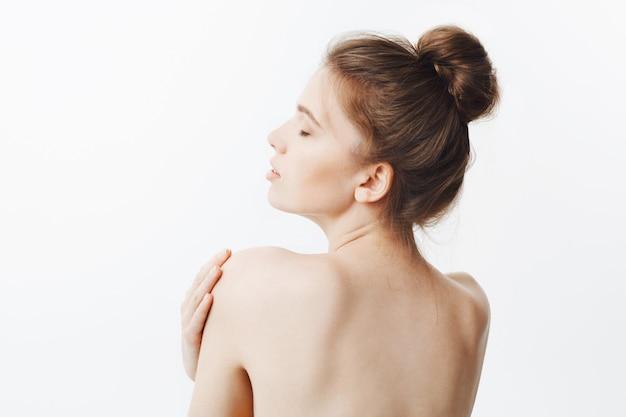 Bauty en gezondheid. knap dun gezond kaukasisch meisje met donker haar in knotkapsel en naakte huid, draait zich om met rug, raakt schouders aan met handen, heeft een ontspannen en hechte look w