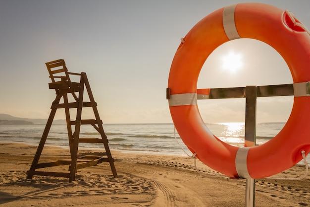 Baywatch-stoel en reddingsring op een strand bij zonsondergang