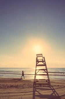 Baywatch-stoel op een prachtig strand bij de zomerzonsondergang. zachte en warme tinten editie. Premium Foto