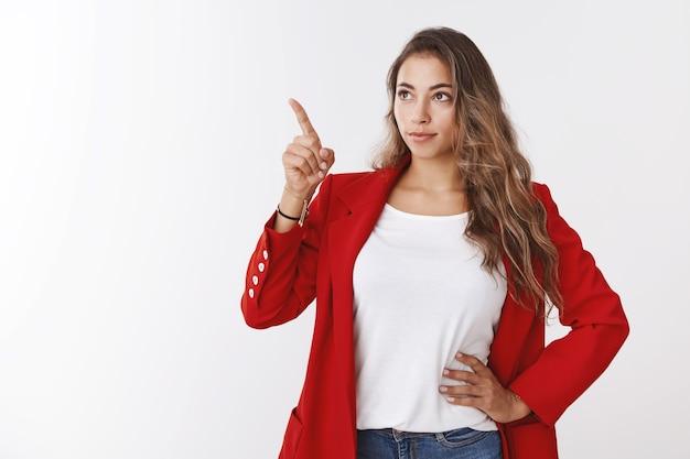 Bazige knappe succesvolle jonge moderne vrouwelijke ondernemer die aanwijzingen geeft aan werknemers die wijsvinger kopieerruimte wijzen op zoek naar linkerbovenhoek serieuze zelfverzekerde blik, witte muur