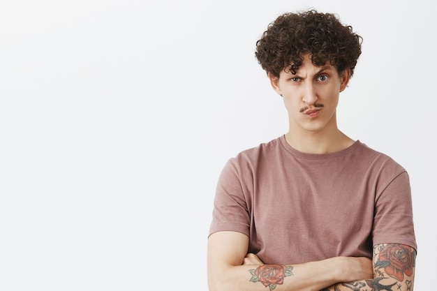 Bazige ontevreden en achterdochtige knappe stijlvolle joodse man met krullend haar en snor in bruin t-shirt hand in hand gekruist op borst grijnzend en fronsend twijfelachtig over grijze muur