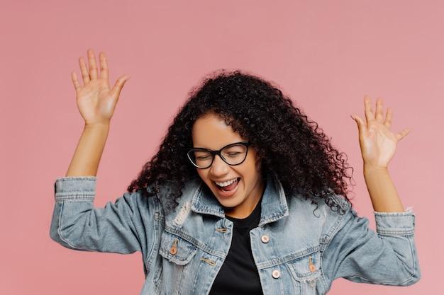 Bbeautiful gelukkige vrouw met krullend kapsel, houdt handen omhoog, lacht van positieve emoties