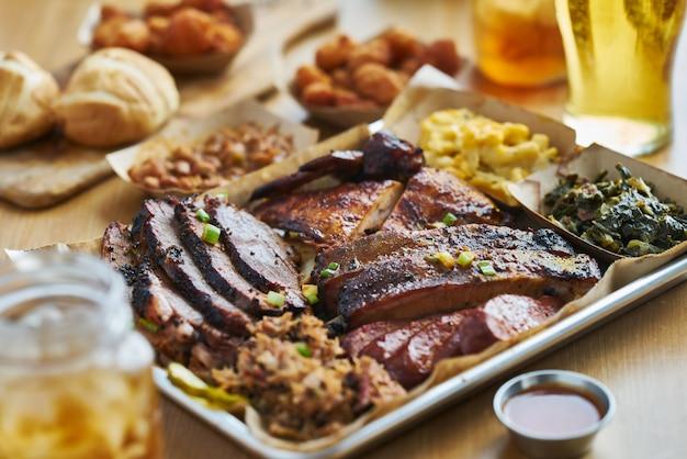 Bbq-dienblad in texas-stijl met gerookte borst, draadjesvlees evenals, kip, hete links en zijkanten