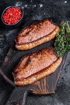 Bbq gegrilde top entrecote of picanha steak op een houten snijplank. zwarte achtergrond. bovenaanzicht.