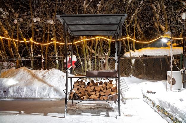 Bbq in de buurt van het huis in de winter. nacht, slingers branden, het sneeuwt. voorbereiding voor het braden van vlees. ze legden geoogst brandhout onder de grill.