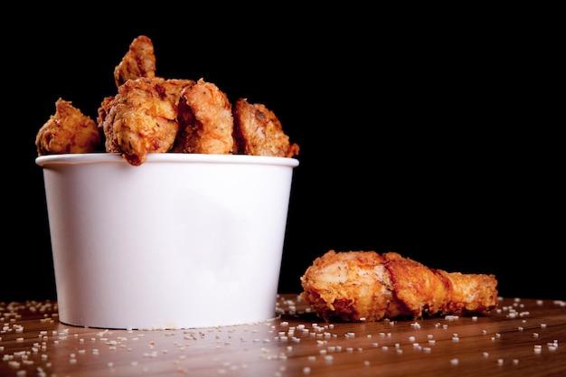 Bbq-kippenbenen in een witte emmer op een houten tafel