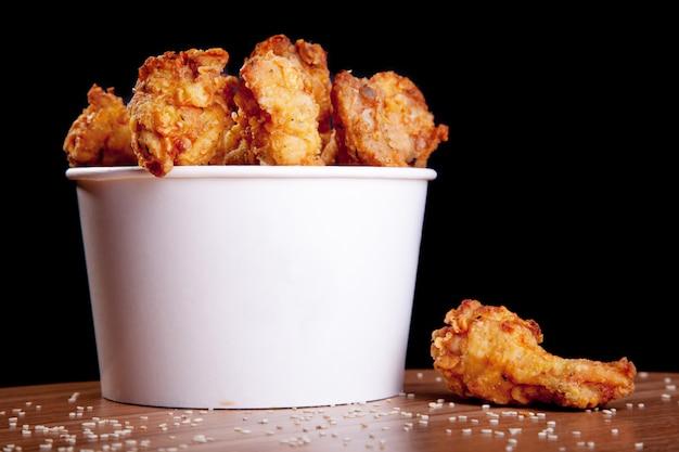 Bbq kippenvleugels in een witte emmer op een houten tafel en een zwarte achtergrond.
