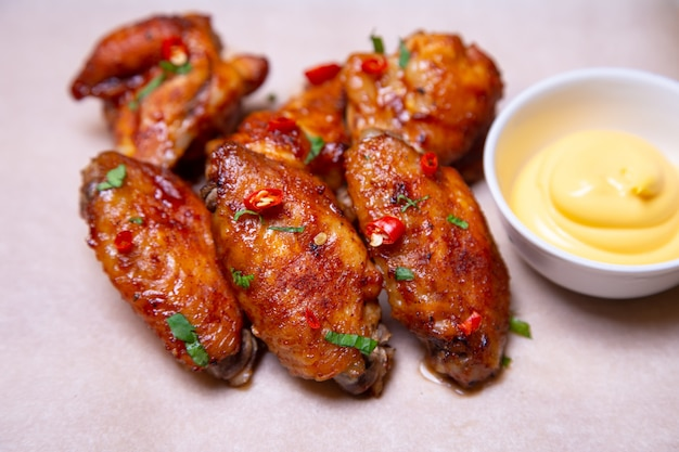 Bbq kippenvleugels met saus op papier. close-up, selectieve aandacht.